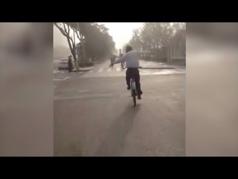 chinese man practices tai chi while riding bike